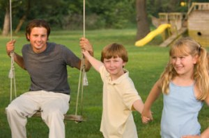 Young Dad on swing with son and daughter